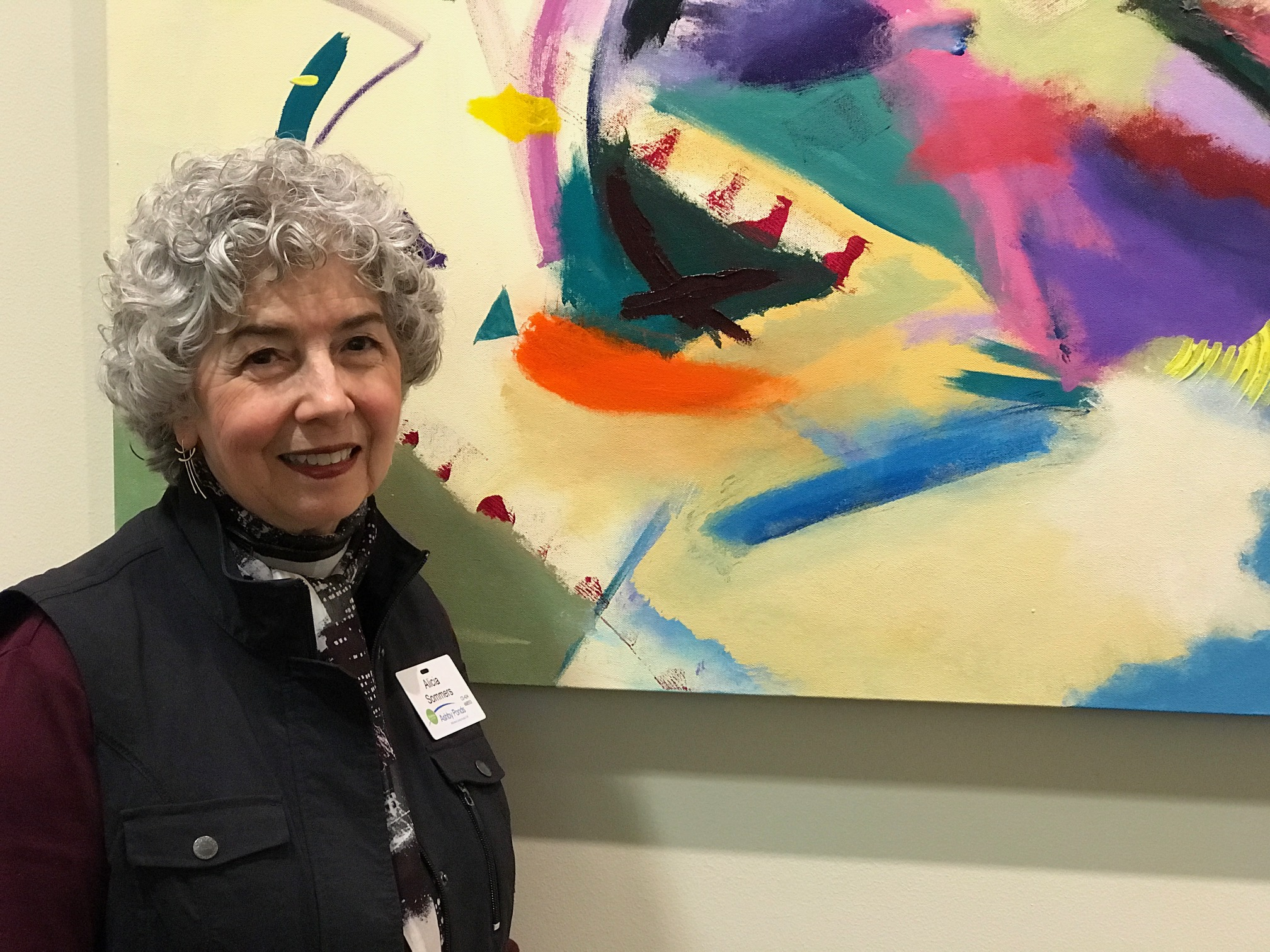 Mrs. Alicia Sommers is photographed with one of her colorful abstract paintings displayed at the Art Gallery of the Great Oak Clubhouse.