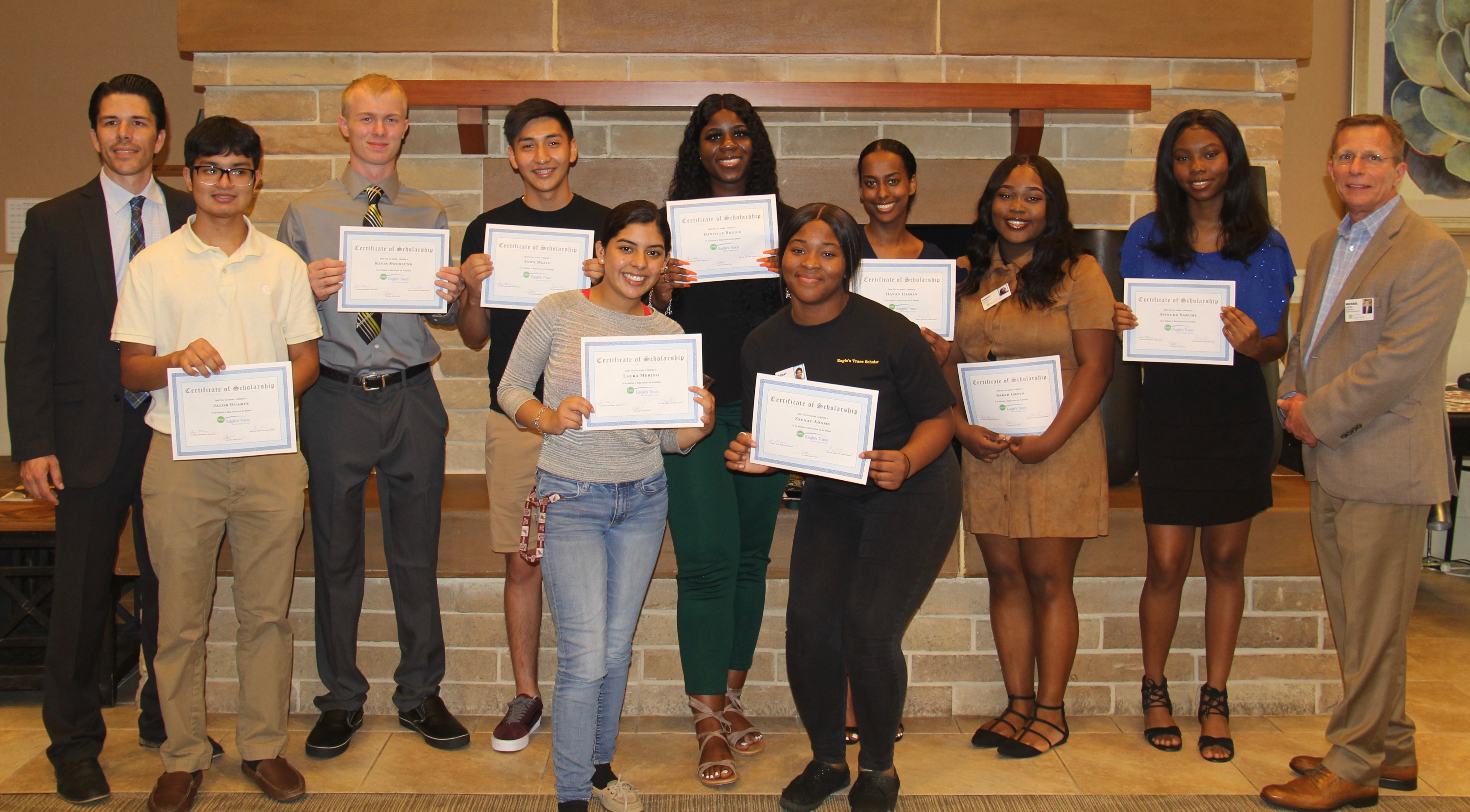 Nine scholar recipients employed at Eagle's Trace pose with two Executive Team members following a ceremony on June 9.