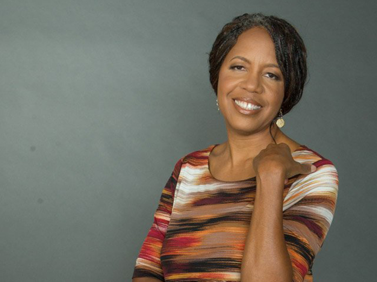 Dr. Lynne Diggs, who is seen in her headshot here smiling and wearing a top colored with brown and red earth tones, became medical director at Riderwood in 2019.