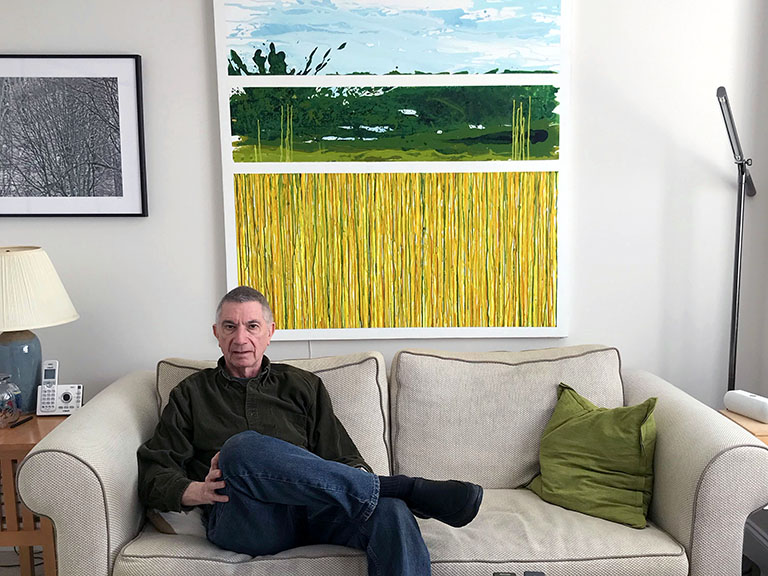 Former high school art teacher Dennis Carroll is seen here on a beige couch in his living room. There is a painting on the wall behind him.