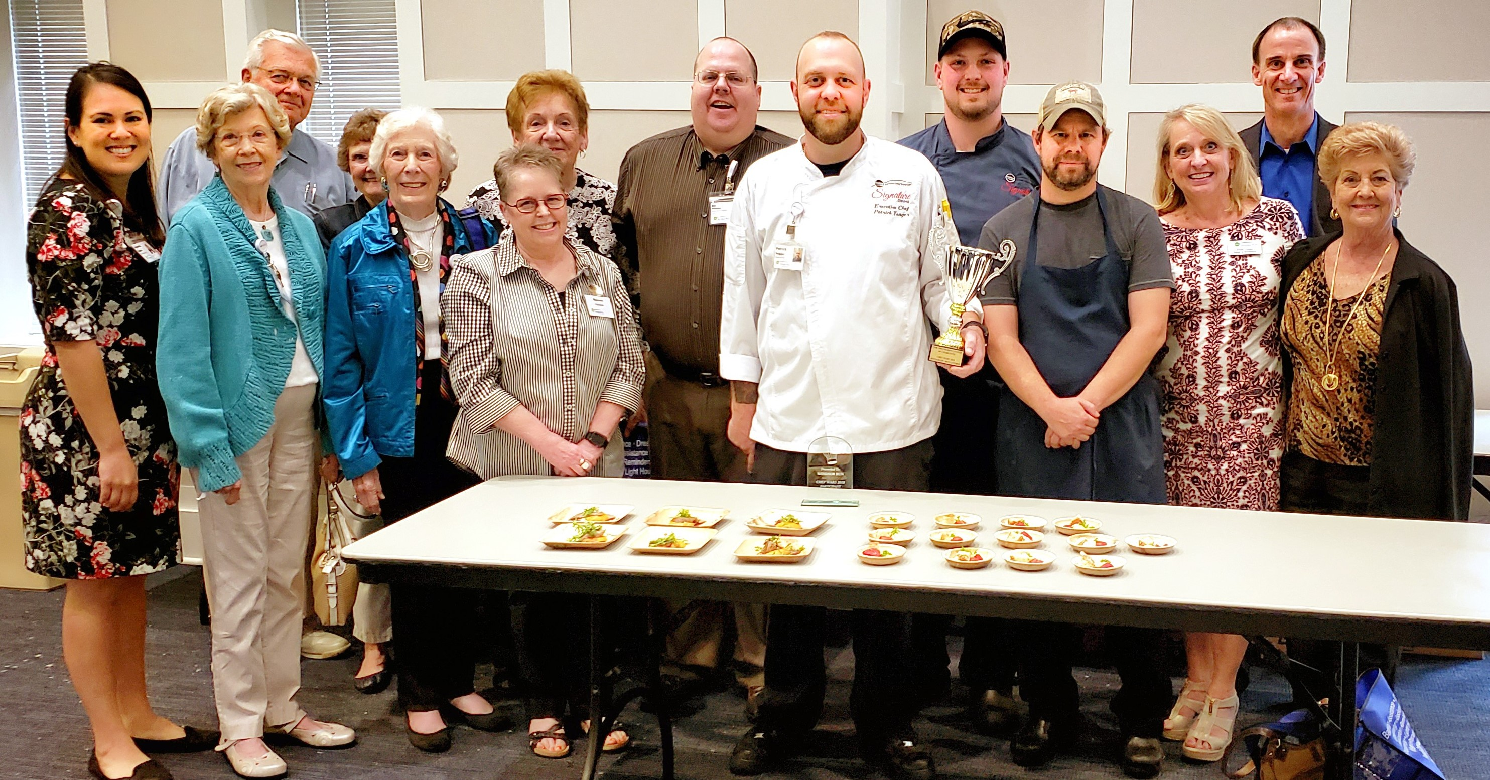 Residents and employees from Windsor Run pose with the trophy and plates of the award-winning entree at the 2019 Chef Wars competition in Charlotte.