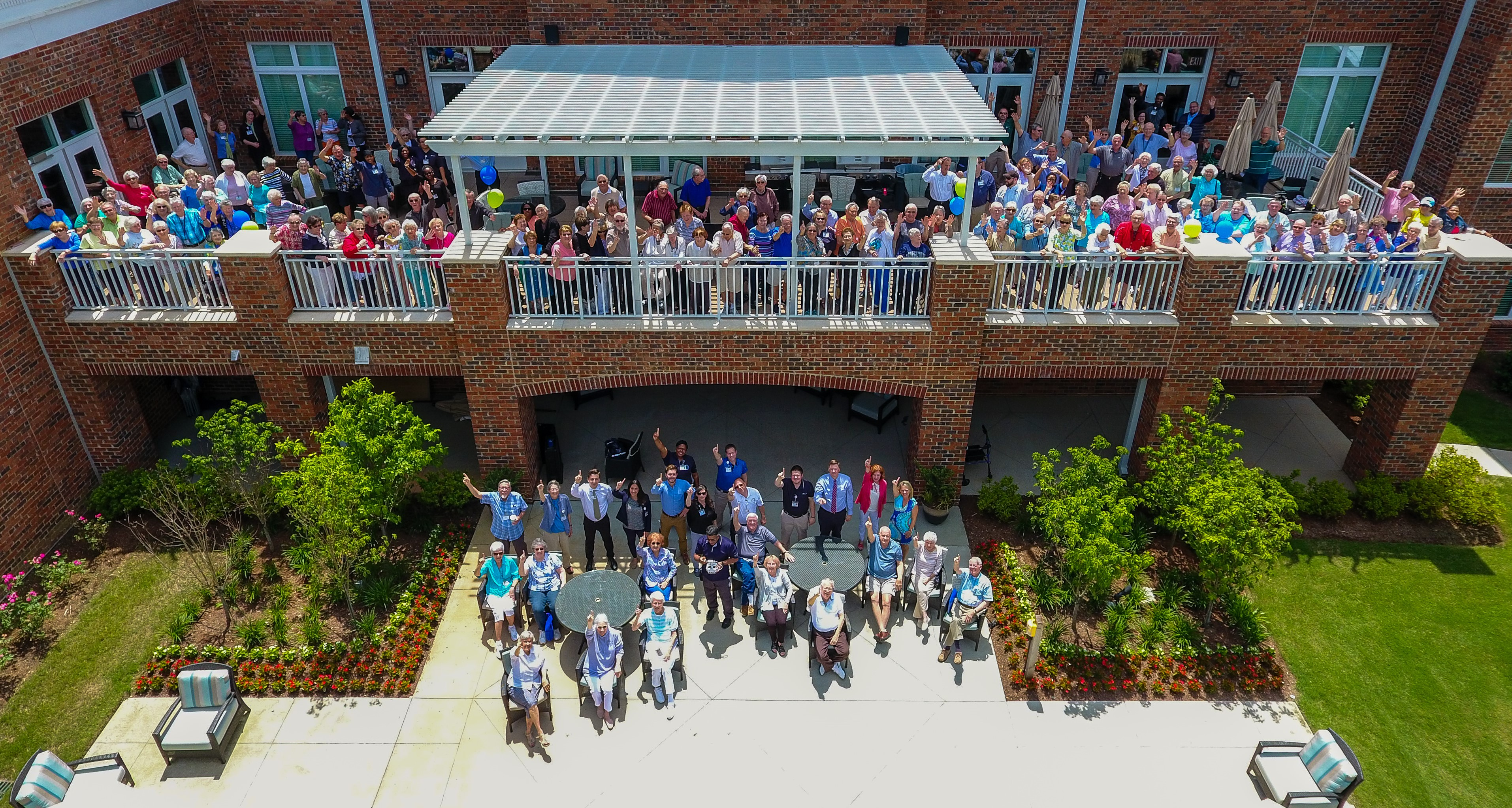 Residents and employees of Windsor Run pose on the deck and patio for a drone photo taken during the first anniversary celebration.