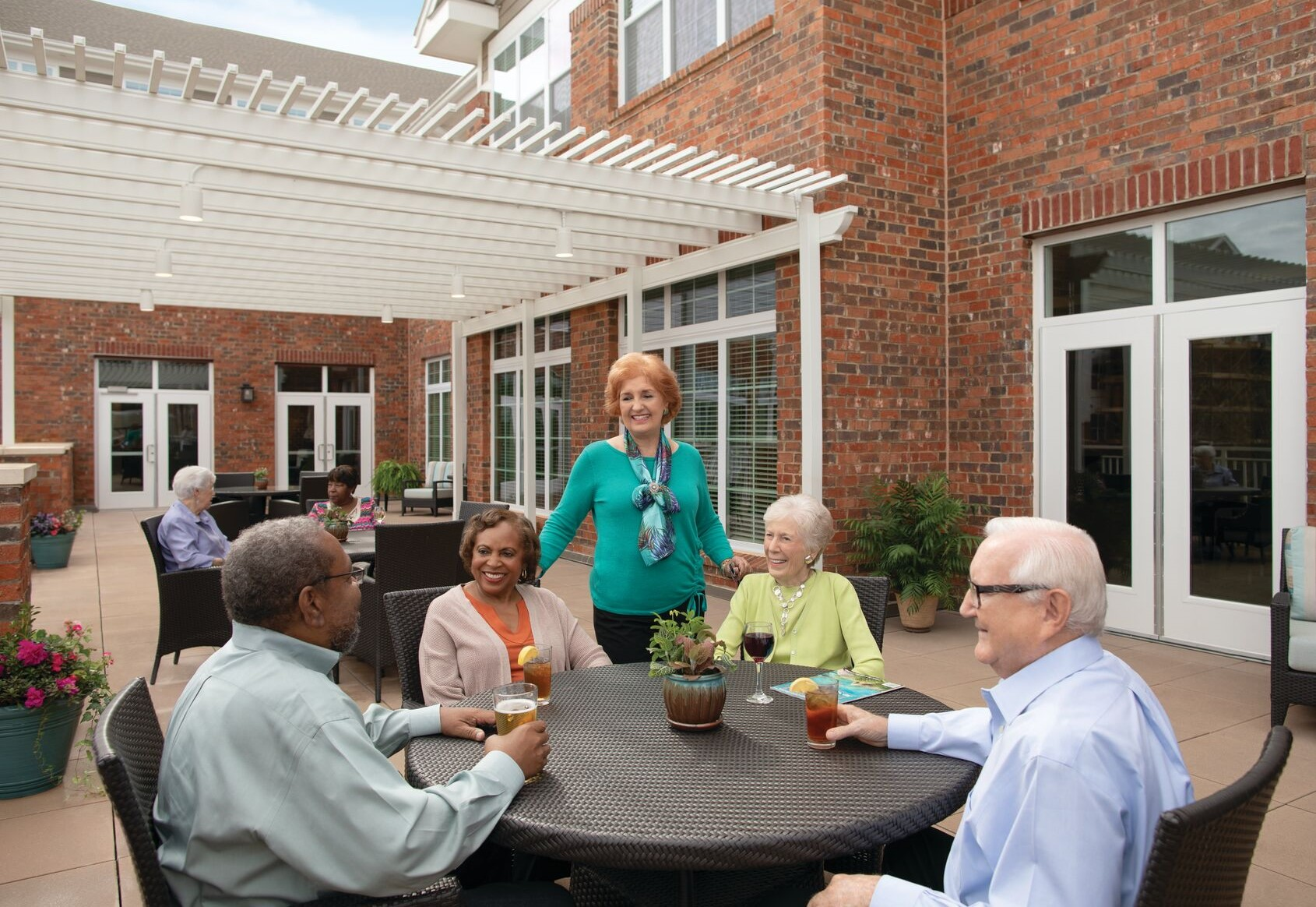 Residents of Windsor Run enjoy a relaxing afternoon outside on the patio at the Erickson Living retirement community.