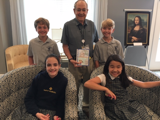 Robert Mack, a resident of Windsor Run, is photographed with students from St. Gabriel School in the community's clubhouse.