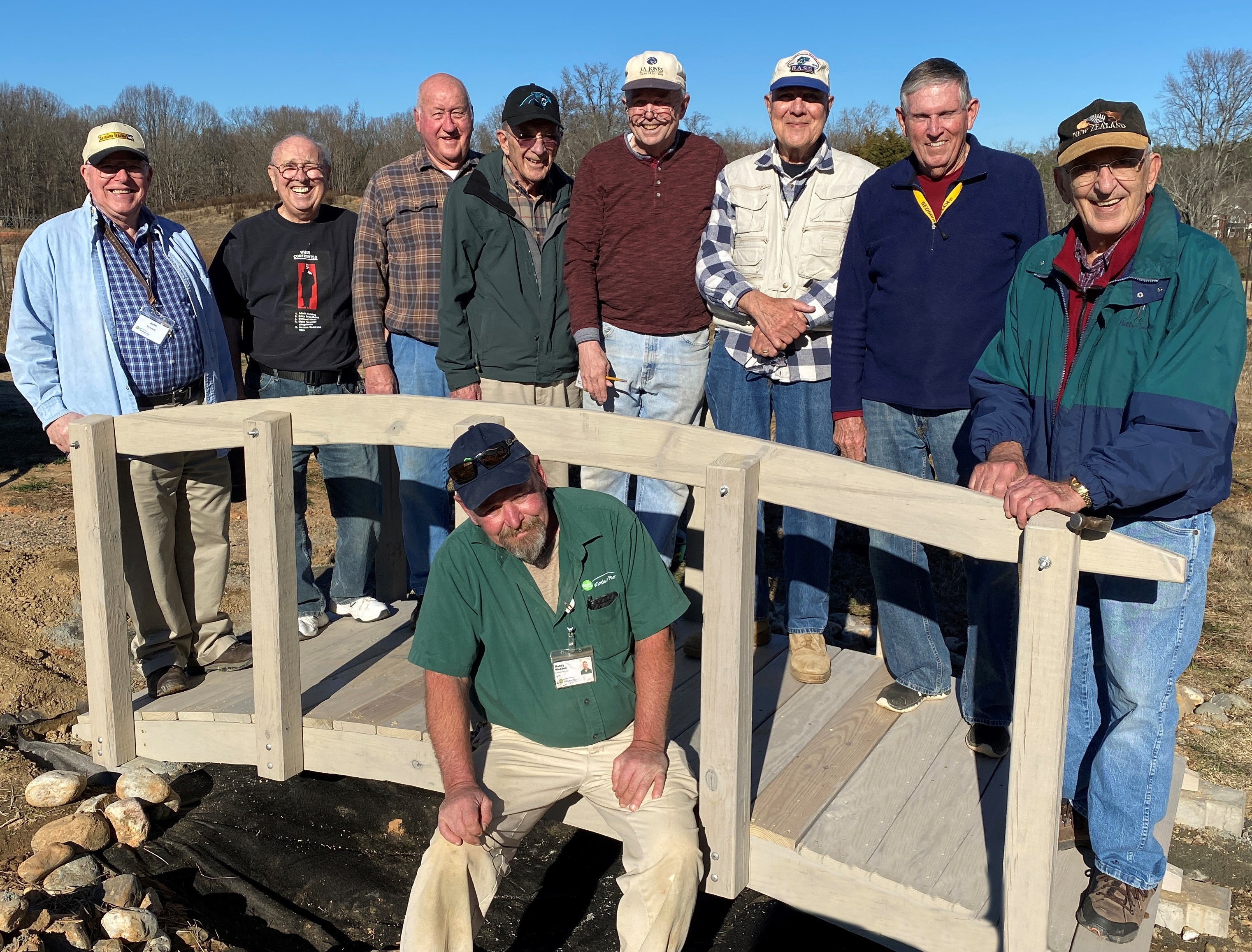 Resident members of the WoodChucks and an employee of Windsor Run are pictured on a new walking bridge they partnered to construct and install.